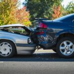Auto wreck with blue car backing into silver car